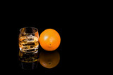 Glass whiskey with ice and Orange on black background