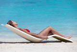 femme qui bronze sur une plage de sable blanc paradisiaque - 107218282