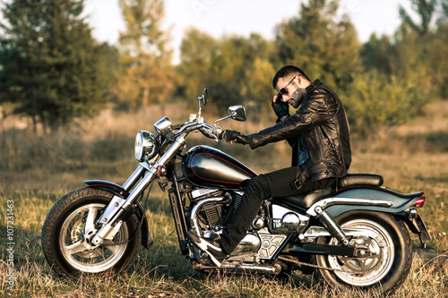 young brutal man in a black jacket and glasses sits near a motorcycle плакат