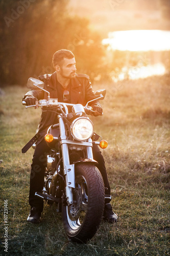 young brutal man in a black jacket and glasses sits near a motorcycle Poster