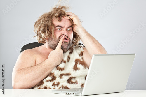 Poster ugly doubtful prehistoric man on laptop
