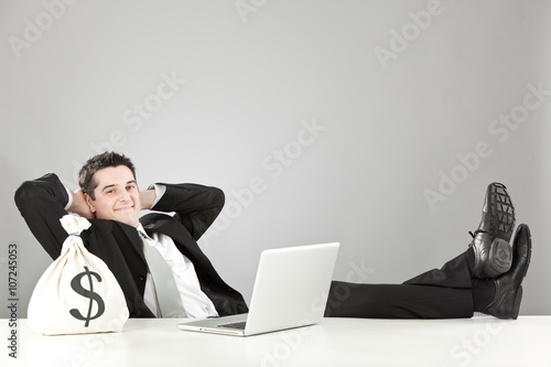 relaxed happy businessman with money bag and laptop isolated on grey Poster