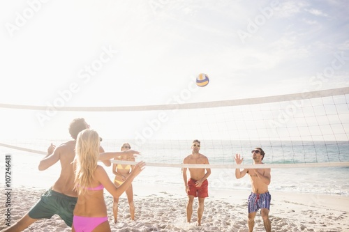 Happy friends playing beach volleyball