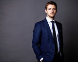 Fototapety Cool businessman standing on grey
