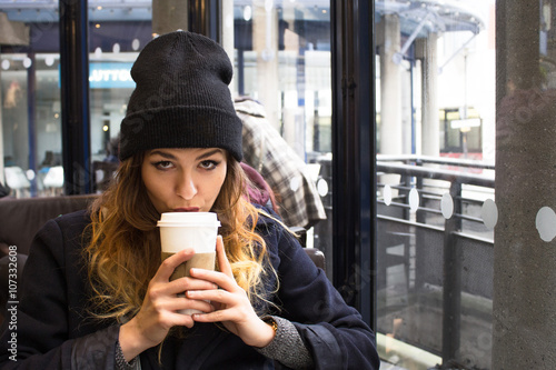 Young attractive girl drinking coffee from a paper cup