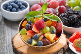 fruit salad in a bamboo bowl and fresh berries, close-up