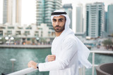 Middle Eastern Arab man standing alone looking at camera at a terrace in Dubai Marina