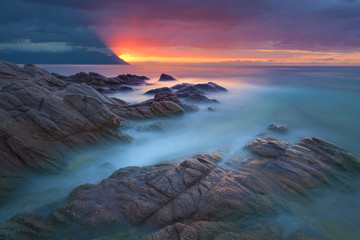 Waves and rocks in motion blur on coastline at dawn