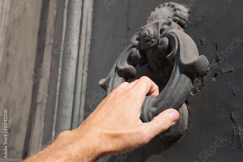 Poster Knocking old black door with metal ring knocker