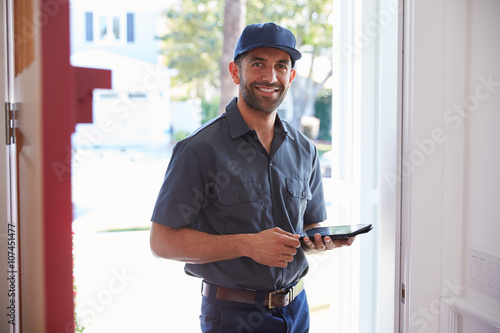 Poster Courier Standing At Front Door With Digital Tablet