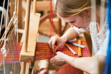 The girl in the production process of textiles are handmade on a loom - 107457002