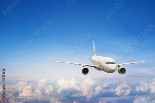 travel by plane, international flight, airplane flying in blue sky above the clouds