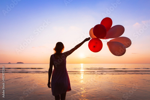 Poster imagination and creativity, girl with multicolored balloons at sunset with copys