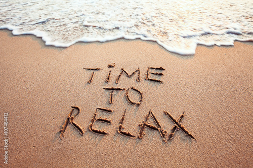 time to relax, concept written on sandy beach - 107484412