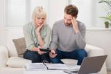 Unhappy Couple Calculating Bills - 107484882