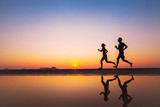 workout, silhouettes of two runners on the beach at sunset, sport and healthy lifestyle background - Fine Art prints