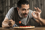 Ragazzo con i capelli scuri con mangia pizza con i pomodorini e fà il segno di ok - sfondo legno scuro e tavolo di legno chiaro