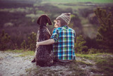 Woman and her dog posing outdoor. Girl loving and hugging tightly her dog and watching landscape. - 107513483
