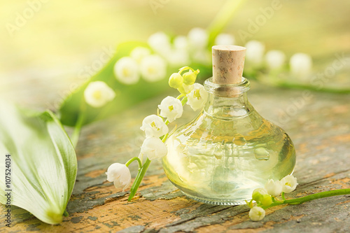 Poster Maiglöckchen - Ätherisches Öl - Flasche und Blüten auf Holz