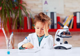 Fototapety tired little scientist writing notes after experiments in school lab