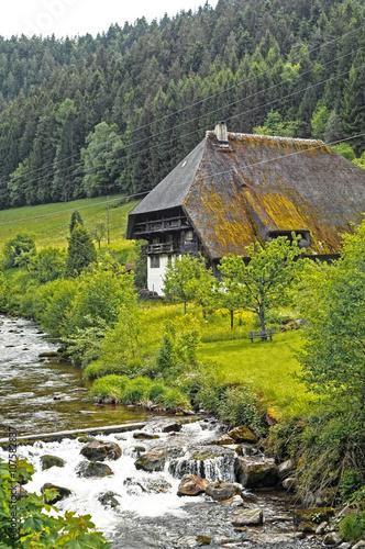 Leinwanddruck Bild altes Schwarzwaelder Bauernhaus am Fluss