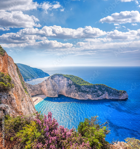 Zdjęcia na płótnie, fototapety na wymiar, obrazy na ścianę : Navagio beach with shipwreck and flowers against sunset on Zakynthos island in Greece
