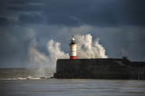 Large sea waves crashing over lighthouse during storm with beaut