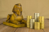 Sphinx and souvenir coins on a wooden table