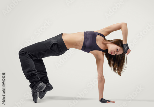 Plexiglas Young girl dancer wearing sport clothes in position arm balance