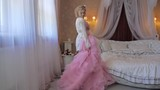 the bride tries on a dress. The bride is going to the wedding. the girl spinning with the dress. Wedding dress pink.