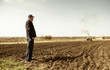 farmer looking at tractor plowing ground at spring season