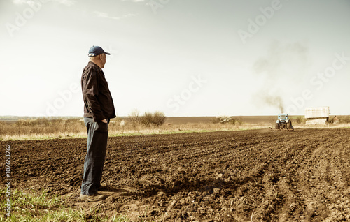 Foto Murales farmer looking at tractor plowing ground at spring season