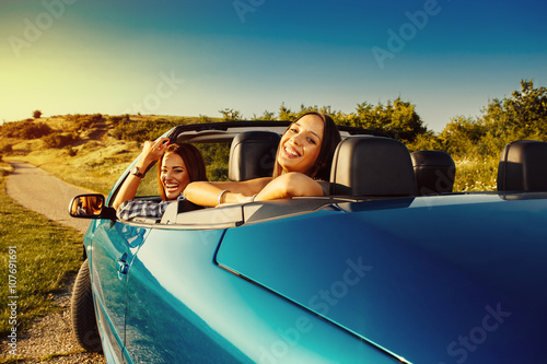 Fotografiet Two attractive young woman having fun in a convertible