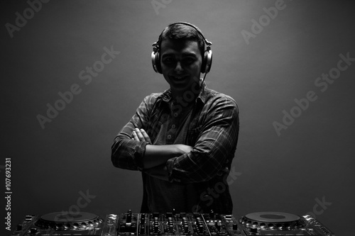 Silhouette of young man, dj with mixer. Back and white photo. Poster