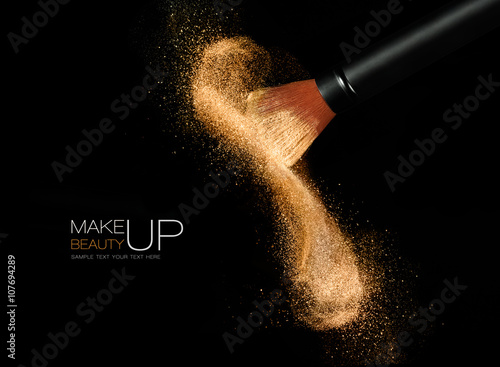 Poszter Cosmetics brush with glowing face powder. Dust explosion