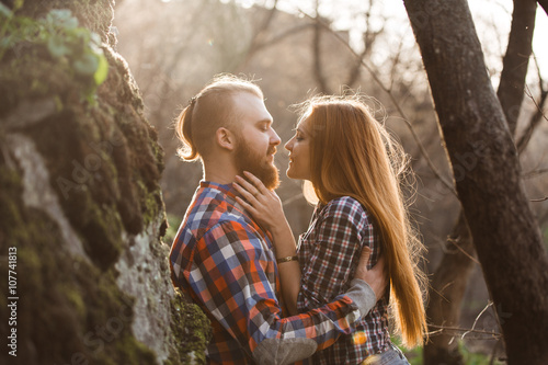 Poster Loving couple, sunset,red-haired people, mountains,a man with a beard