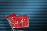 Composite image of trolley with sale shopping bags