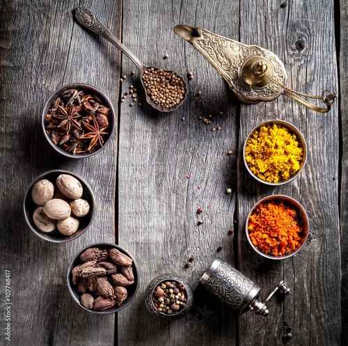 Spices at wooden table - 107768417