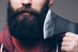 Fototapety Close up of beard Confident young bearded man carrying a big axe on shoulder and looking at camera while standing against grey background