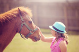 Pony Standing with Little Girl Outside - 107781650