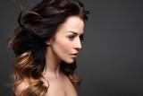 Fototapety Loki, włosy pełne objętości. Portret pięknej kobiety na czarnym tle.