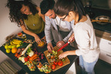 Young group of friends  in kitchen preparing together vegetarian meal.Preparing fruit salad.