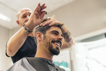 Hairstylist making men's haircut to an attractive man.