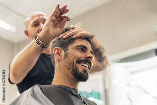 Papiers peints Salon de coiffure Hairstylist making men's haircut to an attractive man.