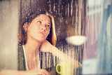 romantic young woman with cup of tea looks at rain through the window
