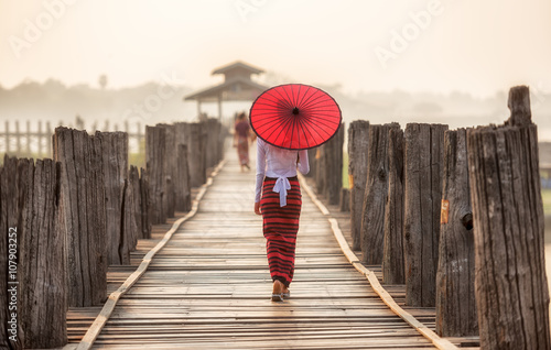 Burmese woman holding traditional red umbrella and walking on U Bein Bridge Poster