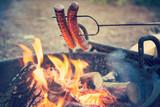 Preparing sausages on campfire