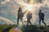 Three friends walk on mountain path in sunny day - 107917875