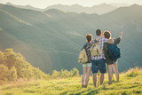 Three friends stand looking at panorama on mountain