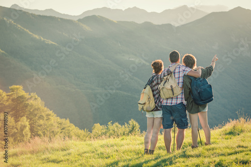 Three friends stand looking at panorama on mountain Poster